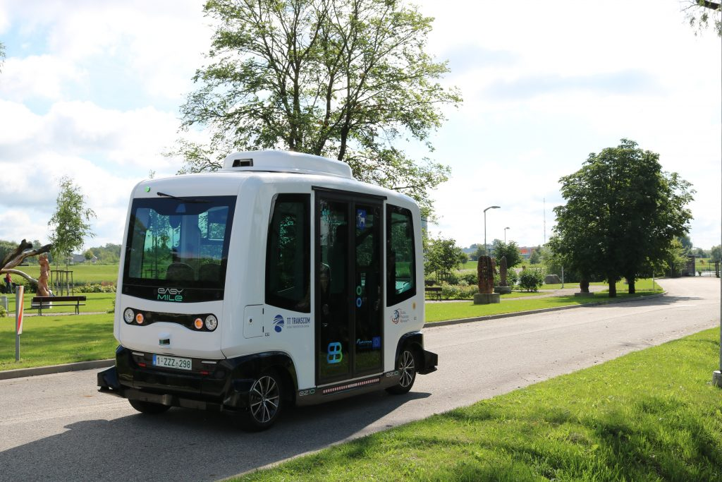 white small automated electric shuttle, pathway, green grass, trees