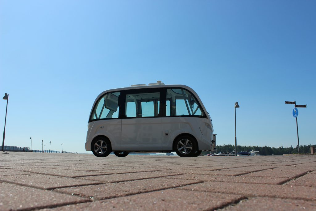 in the front stone pavement, in the middle an automated electric shuttle, in the background clear blue sky