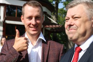 Two men smiling, one thumb up.